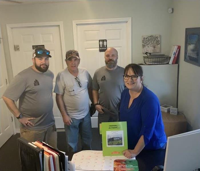 Woman and three men standing behind desk. Woman holding SERVPRO ERP