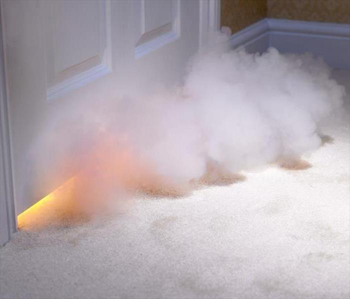 Smoke billowing out from under a door.