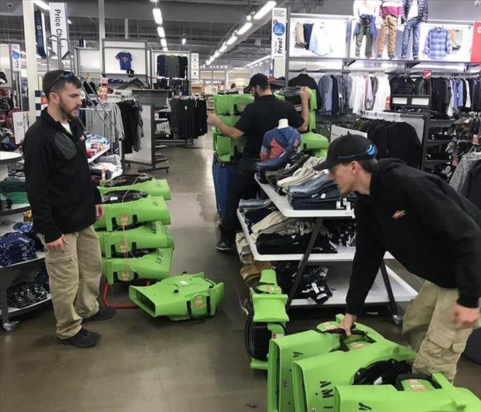 SERVPRO West Pensacola workers, working in a clothing store that has fire damage.