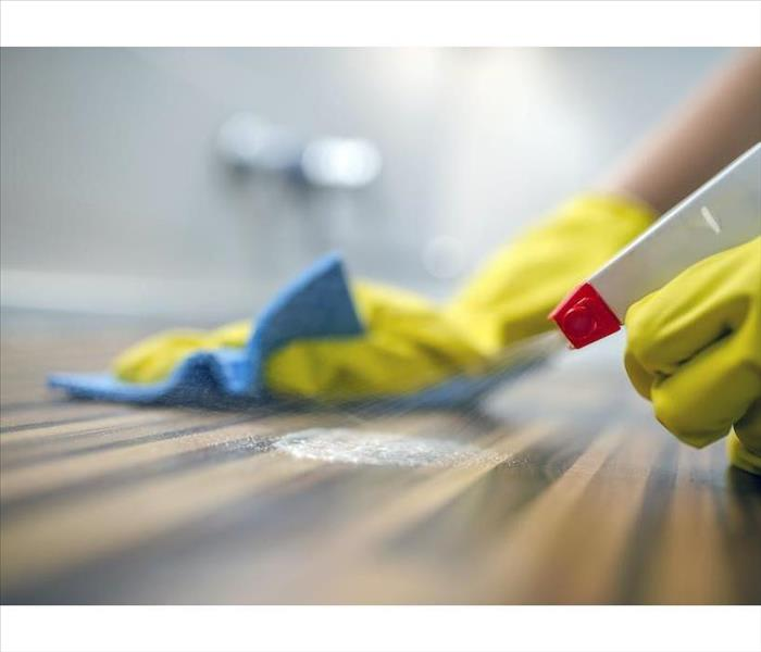 yellow gloved hands spraying a wood surface and holding a blue rag