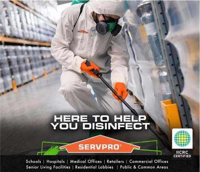 a person in protective gear and mask spraying a disinfectant with the SERVPRO logo beneath as well as an IICRC certification