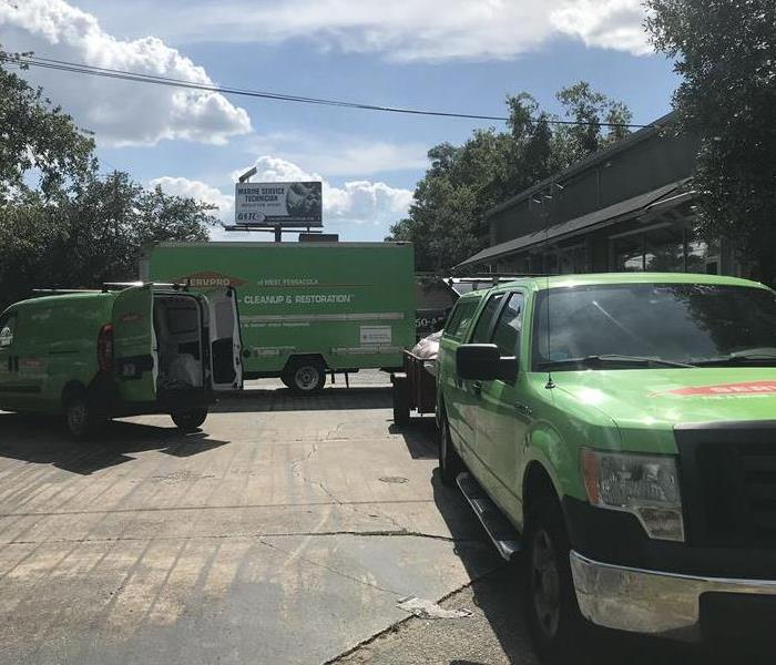 Three SERVPRO vehicles parked in front of a building.